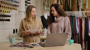 dos sastres de correo electrónico usando una computadora portátil y discutiendo muestras de color en el trabajo. diseñadores de moda o costureras examinan muestras de tejidos en el taller de su propio estudio foto