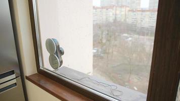 Asistente de robot doméstico limpiando la ventana de vidrio. Ventana de limpieza con aspiradora en edificio alto al aire libre. foto