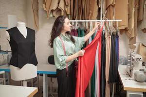 Female fashion designer works on new womenswear collection for clients in cozy workshop studio, dressmaker, tailor or needlewoman standing near clothing rack with fashionable stylish handmade clothes photo