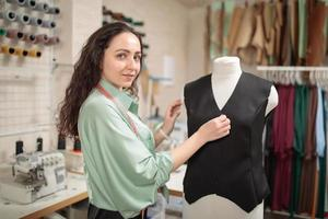 Young female dressmaker adjusting clothes on tailoring mannequin or dummy. Small tailor business in own design studio photo