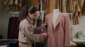 female tailoring fashion designer measuring suit jackets on mannequin dummy in workshop studio atelier. photo