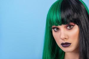 beauty portrait of young woman wearing green black halh color wig, black lips makeup, clean skin. blue backgound. photo