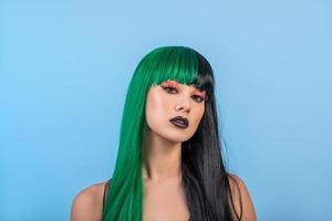 portrait of young woman wearing green black halh color wig, black lips makeup, clean skin. blue backgound. photo