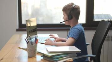 Distance education online learning lesson concept. Child Little school Boy Kid schoolboy children using tablet laptop computer for homework at home. screen monitor Coronavirus COVID-19 quarantine 4 K photo