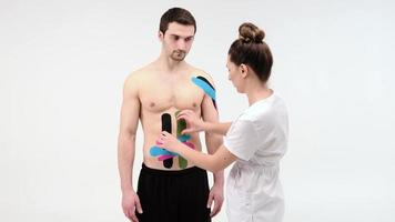 Female therapist applying kinesiology tape on a man's abdomen. Woman prepares male patient to glue kinesio adhesive tape on his belly or abdomen photo