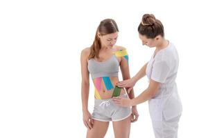 physiotherapist's hands apply colored kinesio tape on the abdomen of young girl. isolated on white background photo