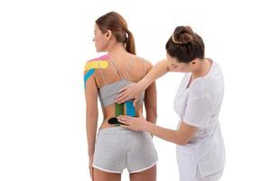 Physical therapist applying kinesio tape on female patient's lower back. Kinesiology, physical therapy, rehabilitation concept. photo