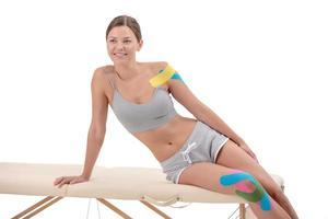Kinesiology taping. Young female athlete isolated on white background with kinesiology tape on shoulder and knee. Fat lose, sport physical therapy,recovery concept. photo