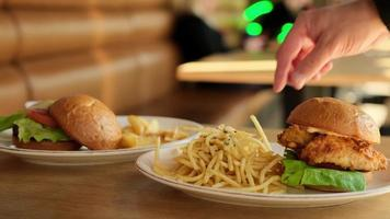 Man's hand was eating French fried, with hamburgers. Eating junk food or fast food for lunch is unhealthy. photo