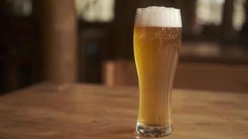 cerveza. Cerveza ligera artesanal fría en un vaso con gotas de agua. pinta de cerveza de cerca sobre un fondo de madera. diseño de borde. foto