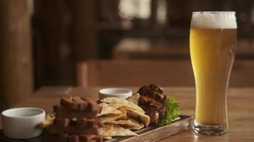 Burbujas de cerveza en vaso sobre la mesa en el pub con bocadillos. Vaso de cerveza fría con burbujas y espuma en el café foto