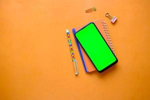top view of smart phone and notepad on orange background photo