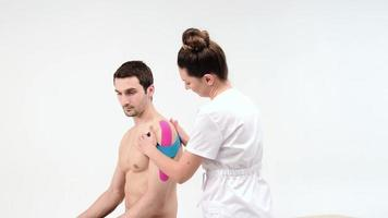 Shoulder treatment with kinesio tape. Physiotherapist applying elastic therapeutic tape to patient shoulder injury photo