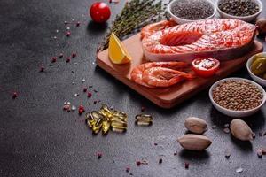 Filete de pescado rojo trucha cruda servido con hierbas y limón foto