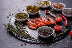 Fine selection of jumbo shrimps for dinner on stone plate photo