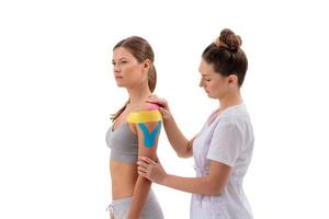 dynamic functional bandage with taping. female specialist glues kinesio tapes on the shoulder of woman photo
