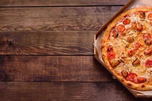 Sabrosa pizza en rodajas con mariscos y tomate sobre un fondo de hormigón foto