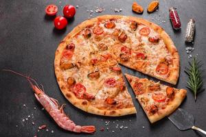 Tasty sliced pizza with seafood and tomato on a concrete background photo