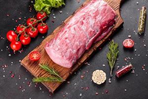 Fresh pieces pork ready to cook on a dark background in the kitchen photo