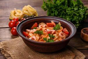 Fettuccine pasta with shrimp, cherry tomatoes, sauce, spices and herbs photo