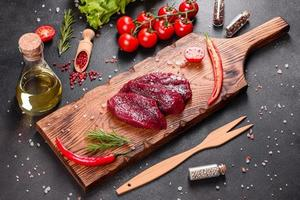 Fresh Raw Beef steak Mignon, with salt, peppercorns, thyme, tomatoes photo