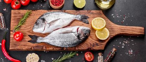 Raw dorado fish with spices cooking on cutting board photo