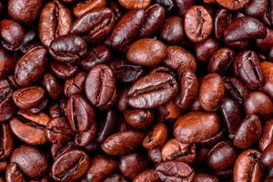 Granos de café recién tostado de cerca contra un fondo oscuro foto