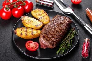Ribeye steak with potatoes, onions and cherry tomatoes photo