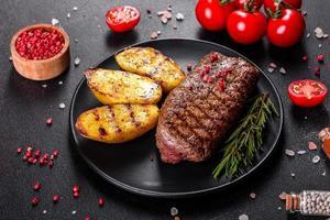 chuletón con patatas, cebollas y tomates cherry foto