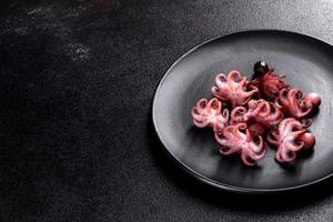 Seafood Baby octopus salad in a black plate photo