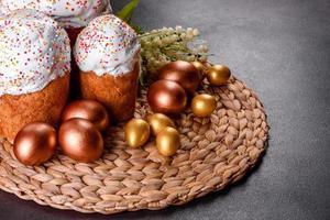 Huevos de pascua de oro y bronce y pastel de pascua sobre un fondo oscuro foto