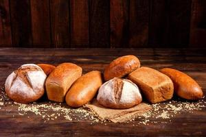 Fresh baked brown bread on a brown wooden background photo
