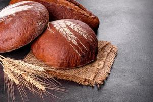 Fresh baked brown bread on a brown concrete background photo