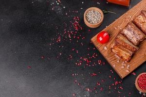 Costillas fritas con romero, cebolla, salsa sobre un fondo de hormigón foto
