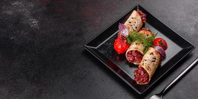 Delicious fresh beef tartar with toasts on a black square plate photo