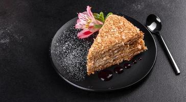 Delicioso pastel fresco napoleón con crema sobre un fondo oscuro foto