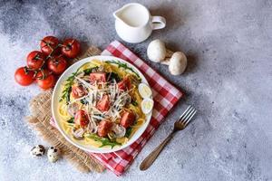 Spaghetti with mushrooms, cheese, spinach, rukkola and cherry tomatoes photo