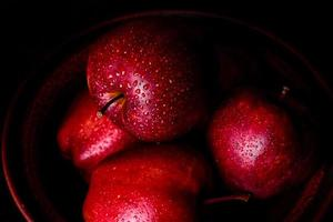 Fresh juicy red apple with droplets of water against dark background photo