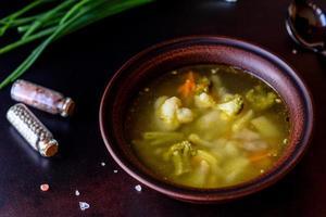 Fresh vegan soup with broccoli, cauliflower, asparagus and carrots photo