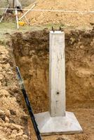 Concrete support is part of foundation of metal high-voltage support photo