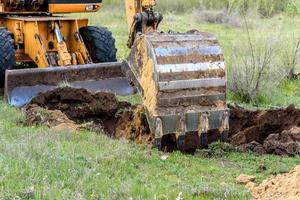 The modern excavator performs excavation work on the construction site photo
