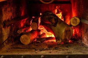 Fire burns inside fireplace to create warmth and atmosphere of comfort photo