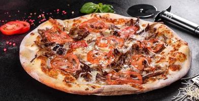 pizza caliente fresca con carne, champiñones, queso y tomates foto