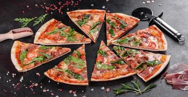 Pizza fresca al horno con rúcula, salami foto