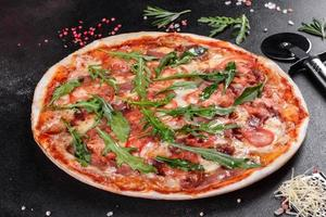 Fresh pizza baked in oven with arugula, salami photo