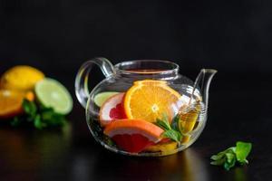 té de frutas caliente con limón, menta, naranja, lima y pomelo foto