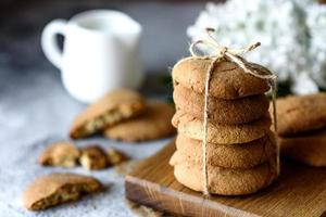 Homemade oatmeal cookies on a wooden cutting board photo