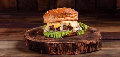 Sabrosa hamburguesa casera a la parrilla con ternera, tomate, queso foto