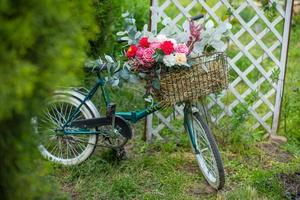 Beautiful bicycle with flowers in a basket stands on an avenue photo