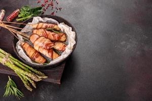 Roll with bacon and chicken mince on a stew with fresh asparagus photo